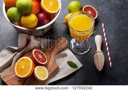 Fresh ripe citruses and juice. Lemons, limes and oranges on dark stone background