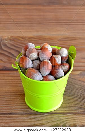 Hazelnuts in a small green bucket on rustic background. Vegetarian food
