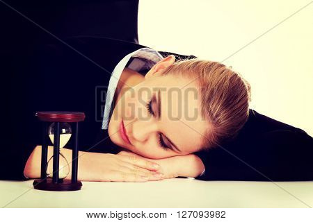 Young business woman sleeping on the desk with hourglass