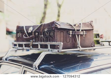 Vintage suitcase on a car roof. Travel with old vintage suitcase tied with a rope to car roof rack.  Retro travel, trip, journey to vacation. Old retro auto. Brown vintage suitcase. Summer travel.