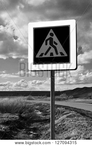 A pedestrian crossing sign on old desert road. Photo traffic sign on a metal pole.