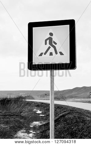 A pedestrian crossing sign on desert road. Photo traffic sign on a metal pole.