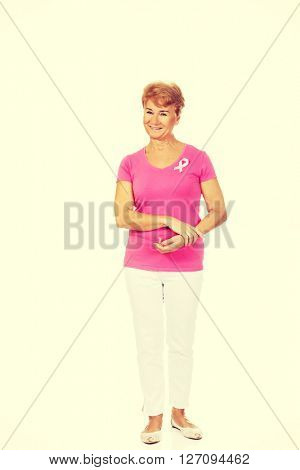 Smiling senior woman with breast cancer awareness ribbon
