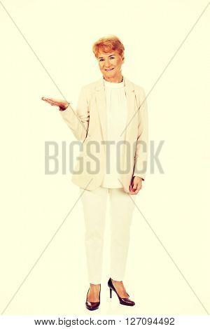 Smile senior woman holding something on open palm