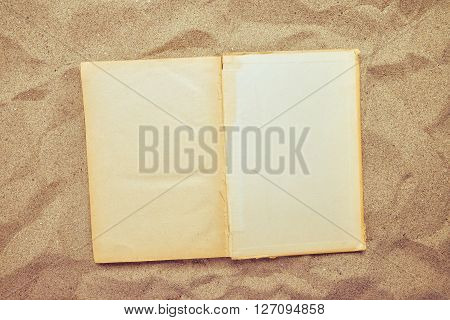 Top view of vintage open book on sandy beach blank pages as copy space reading favourite book on summer vacation holiday in tropical resort.