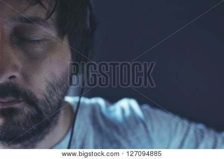 Man listening to music with eyes closed adult unshaven male enjoying favorite song on headphones half face low key portrait
