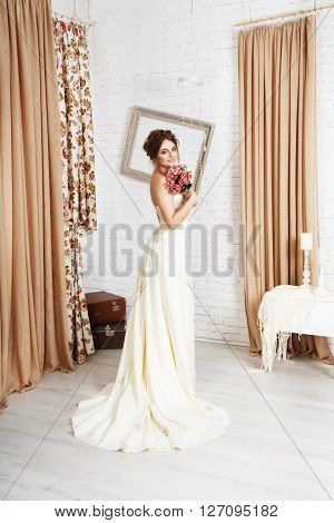 Wedding dress fashion. Beautiful young bride in vintage, shabby chic wedding dress with bridal bouquet. Girl model in champagne color rustic dress in decorated interior, studio shot, high key