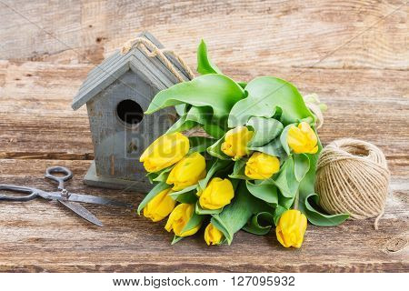 Bright  yellow tulips  with birdcage on wooden desktop
