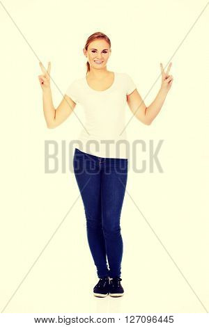 Smiling young woman showing the victory sign