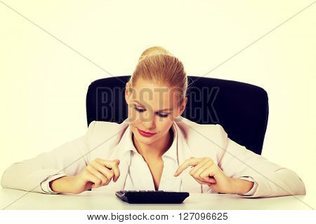 Young smile business woman sitting behind the desk and using calculator