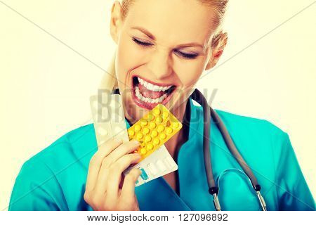 Young female doctor or nurse try to eat few packs of pills