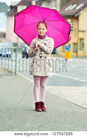 Outdoor portrait of a cute little girl in a city with big pink umbrella, wearing beige coat, red shoes and pink tights