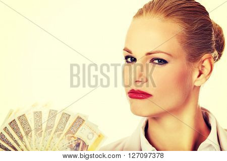Business woman holding a clip of polish money
