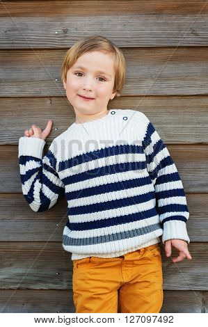 Fashion vertical portrait of adorable little boy of 4-5 years old wearing warm white pullover with blue stripes and yellow trousers, standing against wooden background