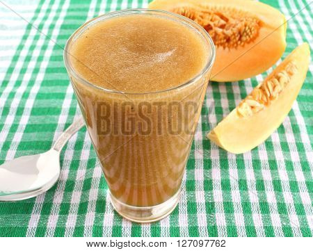 Healthy drink cantaloupe juice and slices of cantaloupe fruit.