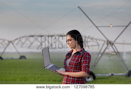Woman With Laptop On Irrigated Field