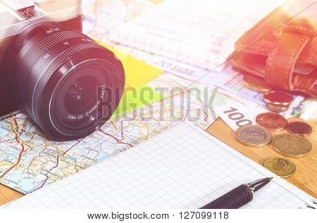 getting ready for travel, money, map and photo camera on wooden table with copy space
