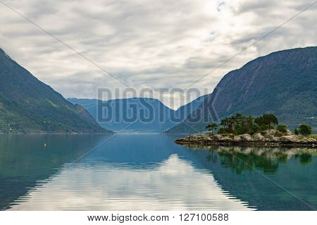 Small rocky and pine island at norwegian fjord with mountains on background