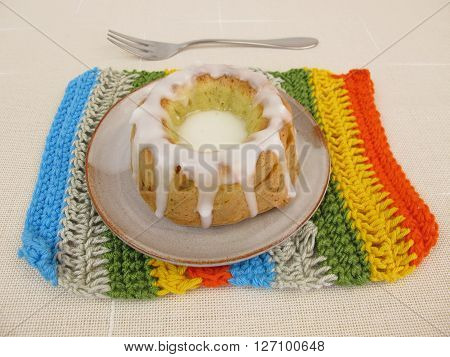 Homemade gugelhupf with sugar icing on crotchet doily