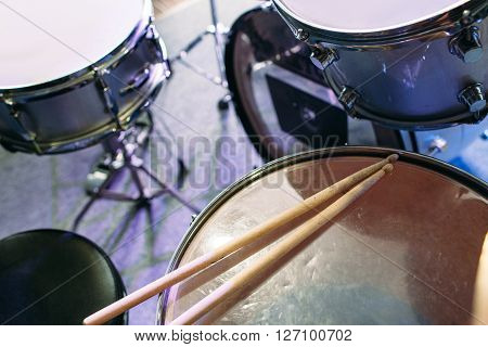 Modern drum set and drumsticks prepared for playing background top view. Flat lay professional drum kit  before a live concert. Drummer, music band, night show, sound recording concept