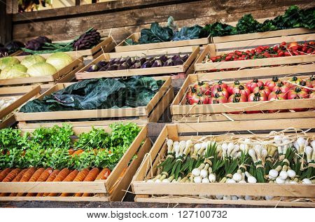 Various vegetables in wooden containers in the rural marketplace. Healthy food. Market gardening.