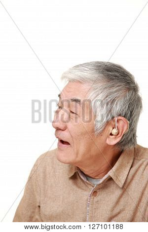 senior Japanese man with hearing aid on white background
