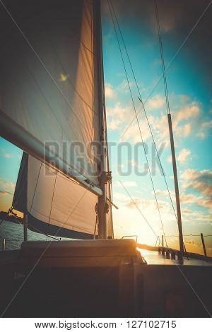 mast yacht at sunset, Sailboat on sunset, luxurious water transport, bright sun light on the sea, evening travel on sail yacht, yachting sport concept