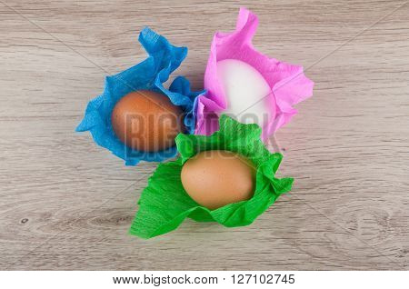 beige brown white chicken eggs in colored green blue pink paper wrapper laying on wooden table. Top view