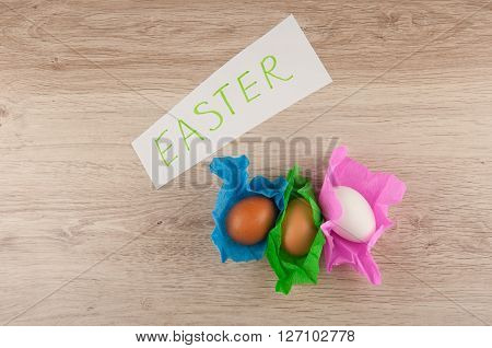 word easter on paper title and three chicken eggs in colored paper wrapper laying on wooden table