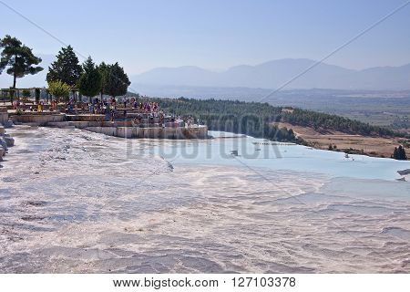 PAMUKKALE, TURKEY - September 13, 2015: Tourists regard the travertines with pools and terraces at Pamukkale. Pamukkale is included in the UNESCO World Heritage List.