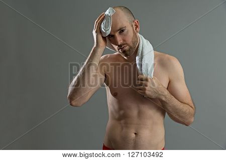 Exhausted sporty man drying his sweat from his forehead. On grey background.