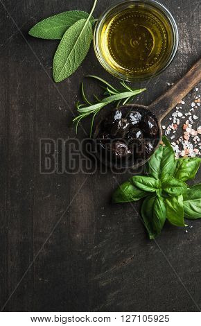 Greek black olives, fresh green sage, rosemary, basil herbs, salt and oil on dark rustic wooden background.  Top view, copy space, vertical