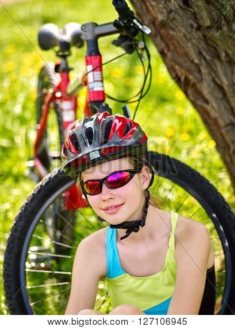 Bikes cycling girl wearing helmet have a rest sitting under tree.