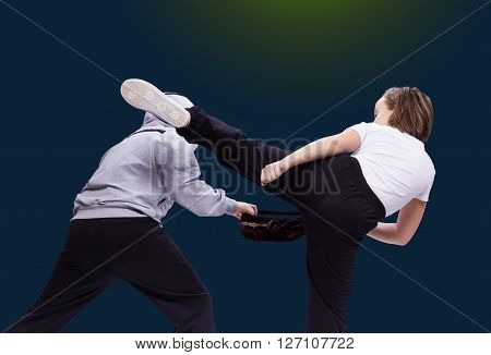 High kick leg beats Woman robber on the light background