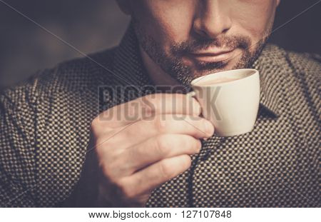 Confident well-groomed bearded man with cup of coffee on dark background.