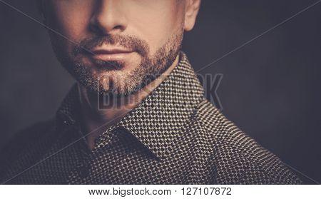 Confident handsome man with beard posing on dark background.