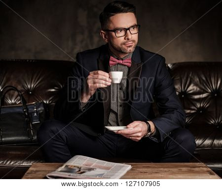 Well-groomed stylish young man with cup of coffee sitting on comfortable leather sofa on dark background.