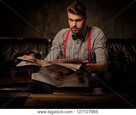 Young handsome old-fashioned bearded man with newspaper sitting on comfortable leather sofa on dark background.