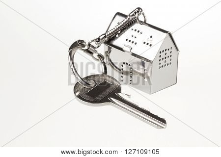 key with keychain in the form of a silver-colored house on a white background