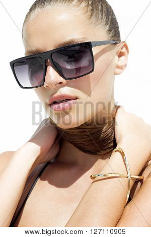 Woman in black sunglasses and swimsuit wearing golden bracelet with hair up poses on isolated white background. Fashion tan model. Beautiful awesome cool girl. Closeup portrait. Phuket, Thailand