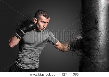 Boxer punching bag blow to the explosion. Young sportsman in black boxing gloves and gray uniforeme on a flat background.