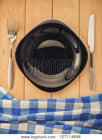 kitchen utensils and cloth napkin on wooden background
