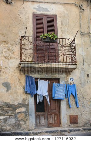 SPERLINGA, ITALY - MARCH, 27: Clothes hanging to dry on a clothes-line next to the door on March 27, 2016