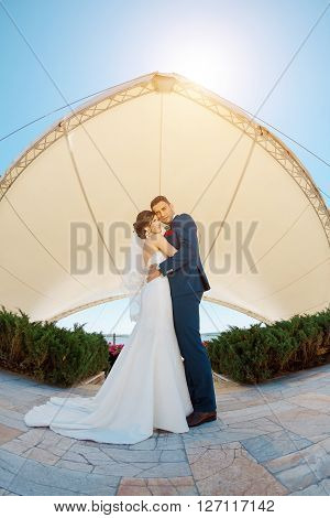 Young wedding couple stand face to face with closed eyes and dream of their future life. Fisheye lens