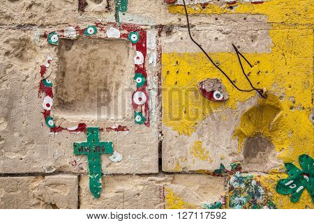 Hand painted wall with religious reference bottle plugs and cross
