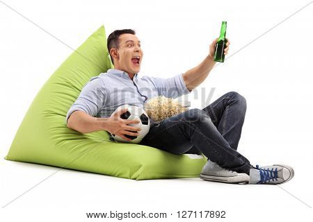 Studio shot of a young soccer fan watching a game with beer and popcorn seated on a beanbag isolated on white background