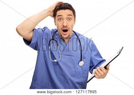 Surprised young doctor in blue uniform holding a clipboard and scratching his head isolated on white background