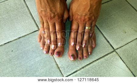 Toes and fingers with bi-color nailpolish on tile floor