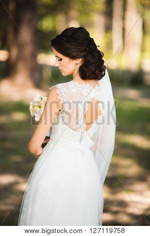 Beautiful sensual young brunette bride in white wedding dress and veil standing in forest holding bouquet outdoor on natural background. Sensual photo of bride's back