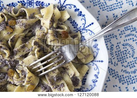 Poppy seed pasta on a blue plate traditional hungarian meal